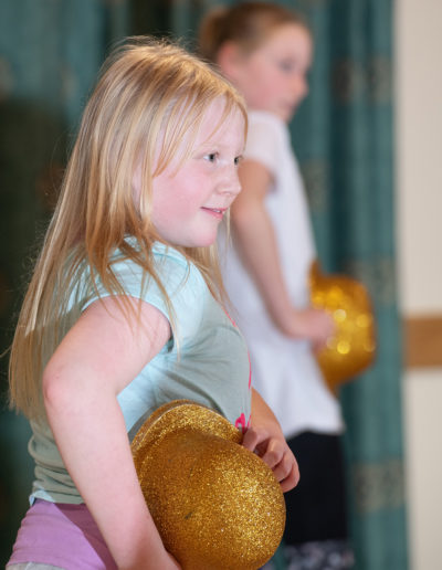 Girl holding gold glitter hat